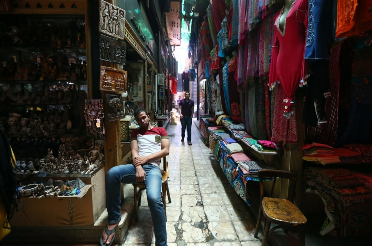 <p>Egyptians wait for customers in an alley of the historic Khan al-Khalil market in downtown Cairo on July 13, 2013. The usually busy market place and a haven for foreigners is almost deserted.</p>
