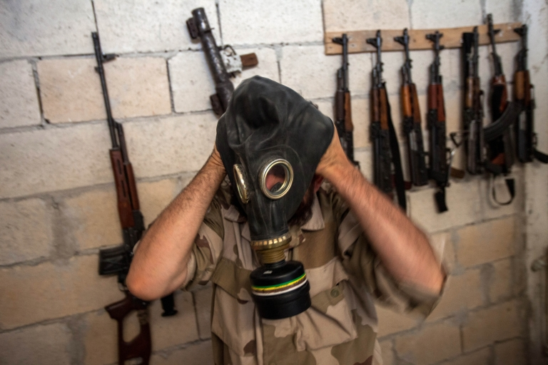 <p>A Syrian rebel tries on a gas mask seized from a Syrian army factory in the northwestern province of Idlib on July 18, 2013. Western countries say they have handed over evidence to the UN that Bashar al-Assad's forces have used chemical arms in the two-year conflict. More than 100,000 people have died in the conflict, which morphed from a popular movement for change into an insurgency after the regime unleashed a brutal crackdown on dissent.</p>