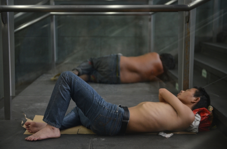 <p>People take shelter from the heat in the entrance of a subway station in Shanghai on July 31, 2013. More than 10 people have died in China's commercial hub, a local health official said as the city swelters in its highest temperatures for at least 140 years.</p>