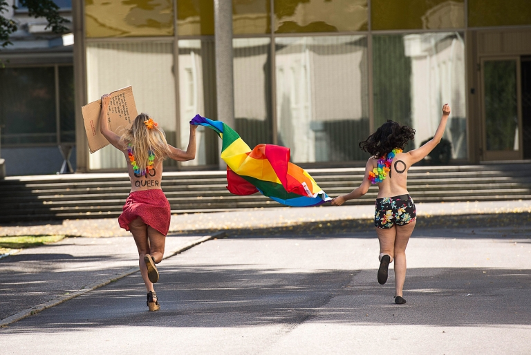 <p>August 1, 2013- Two topless Femen activists run as they hold up a rainbow flag and a sign saying: