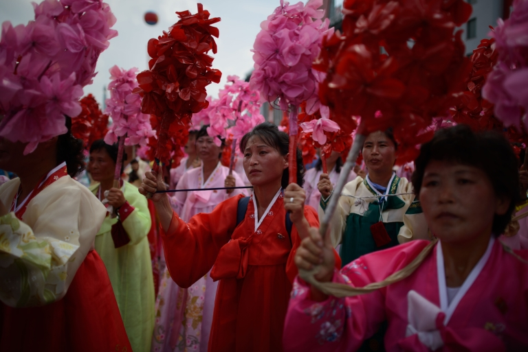 <p>North Korean wave flowers as they stand on Kim Il-Sung square during a parade marking the 60th anniversary of the Korean war armistice in Pyongyang. North Korean leader Kim Jung Un is facing a dearth of</p>