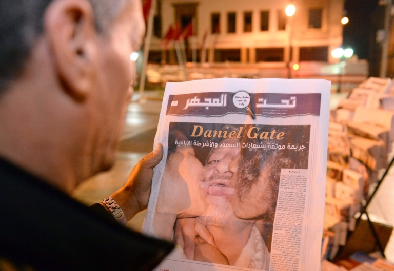 <p>This photo taken on August 5, 2013 shows a man in Rabat reading about a Spanish pedophile who raped 11 local children. Spanish police have arrested convicted pedophile Daniel Galvan Vina, who had his pardon revoked by Morocco's King Mohamed VI after it sparked angry protests in the north African country.</p>