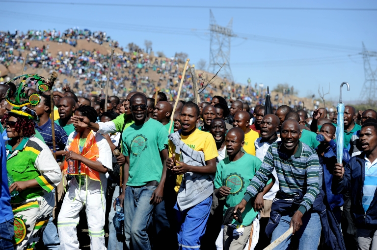 <p>Co-workers and relatives of 34 miners shot dead by South African police during a violent wage strike sing and dance as they gather on August 16, 2013 in Marikana to mark the first anniversary of their deaths. The day marked a year after police opened fire on thousands of strikers at platinum producer Lonmin's mine, northwest of Johannesburg.</p>