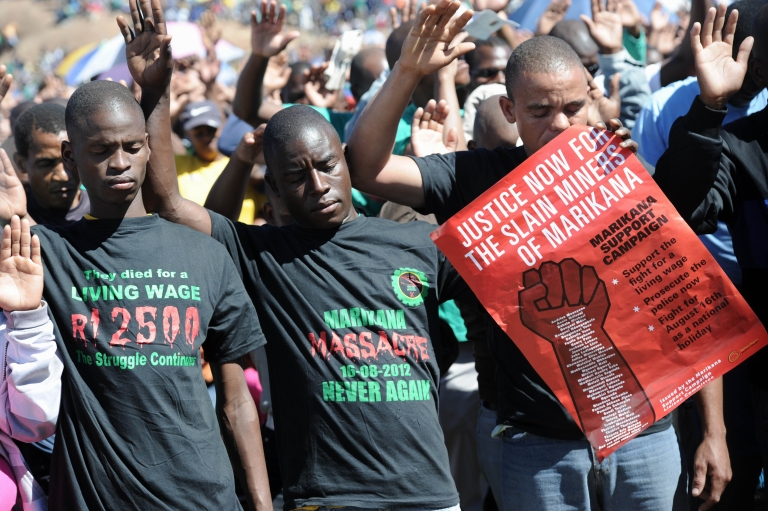 <p>Co-workers of 34 miners shot dead by South African police during a violent wage strike pray during a ceremony to mark the first anniversary of their deaths on August 16, 2013 in Marikana. Today marks a year after police opened fire on thousands of strikers at platinum producer Lonmin's mine, northwest of Johannesburg, which killed 34 and injured 78 people. The August shooting was described as the worst police brutality since the end of apartheid two decades ago.</p>