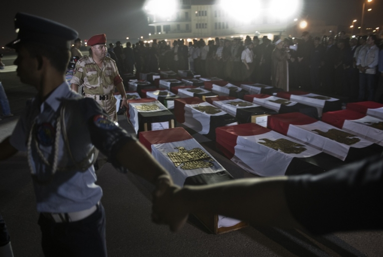 <p>Egyptian army surround coffins covered with the national flags at Almaza military airbase in Cairo on on August 19, 2013, during a funeral for 25 policemen who were killed near the border town of Rafah, North Sinai.</p>