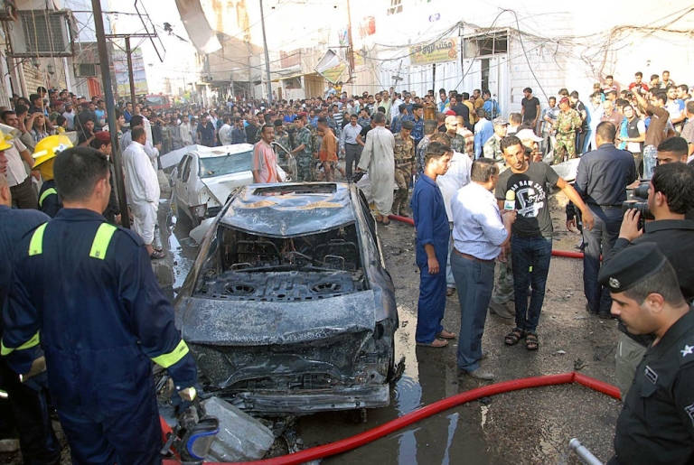 <p>A picture taken on August 19, 2013 shows Iraqis gathering near the remains of vehicles at the scene of a car bomb explosion in Nasiriyah, south of the Iraqi capital Baghdad.</p>