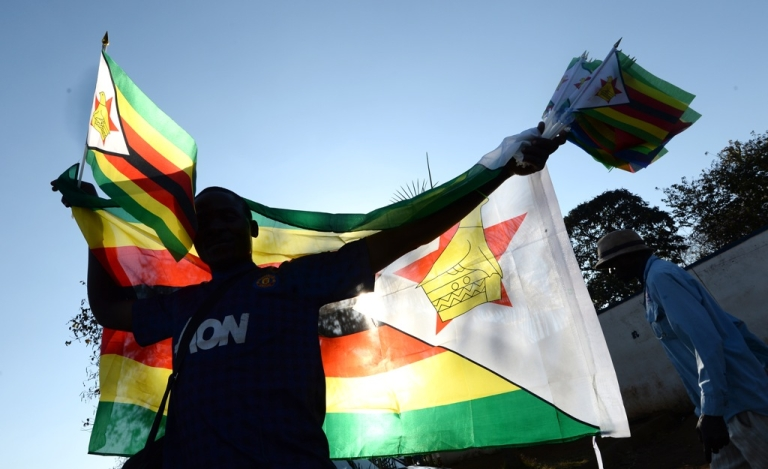 <p>A vendor sells flags in a street in Harare on August 21, 2013, on the eve of Zimbabwean President's inauguration ceremony. President Robert Mugabe's swearing-in will be held at The National 60,000-seat sports stadium on August 22.</p>