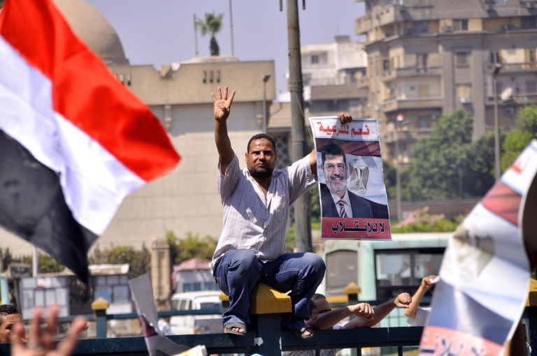 <p>Supporters of the Muslim Brotherhood and Egypt's toppled president Mohamed Morsi (portrait) demonstrate in Cairo on August 30, 2013.</p>