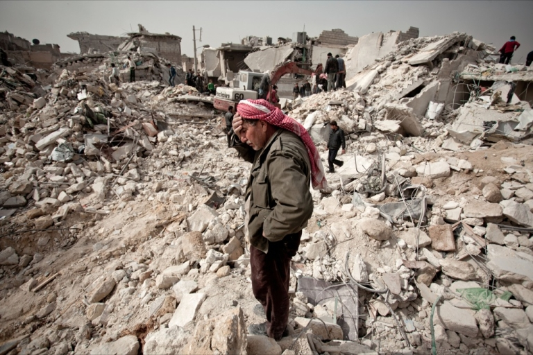 <p>A Syrian man reacts while standing on the rubble of his house while others look for survivors and bodies in the Tariq al-Bab district of the northern city of Aleppo on February 23, 2013.</p>