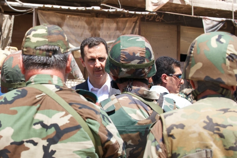 <p>This photograph from the Syrian Presidency's Facebook page shows Bashar Assad meeting troops on Army Day, Aug. 1, 2013.</p>