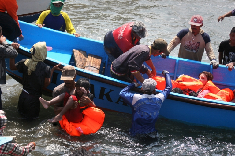 <p>Rescuers assist survivors arriving on fishing boat at the wharf of Cidaun, West Java on July 24, 2013 after an Australia-bound boat carrying asylum-seekers sank off the Indonesian coast.</p>