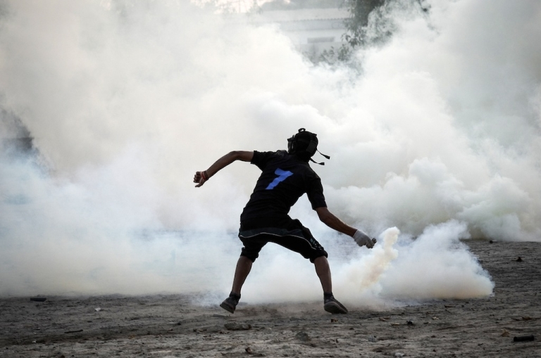 <p>A Bahraini protestor throws back a tear gas canister fired by riot police during clashes following an anti-regime protest in the village of Abu Saiba, west of Manama, on August 15, 2013.</p>