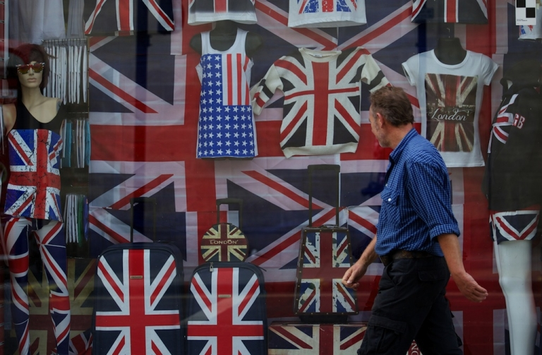 <p>A man walks past the window of a shop selling clothing and goods bearing the Union Flag in London on August 7, 2013.</p>