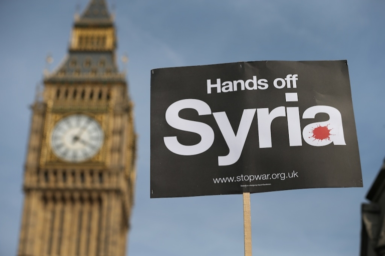 <p>LONDON, ENGLAND - AUGUST 29: A peace campaigner holds up a placard outside Parliament on August 29, 2013 in London, England.</p>