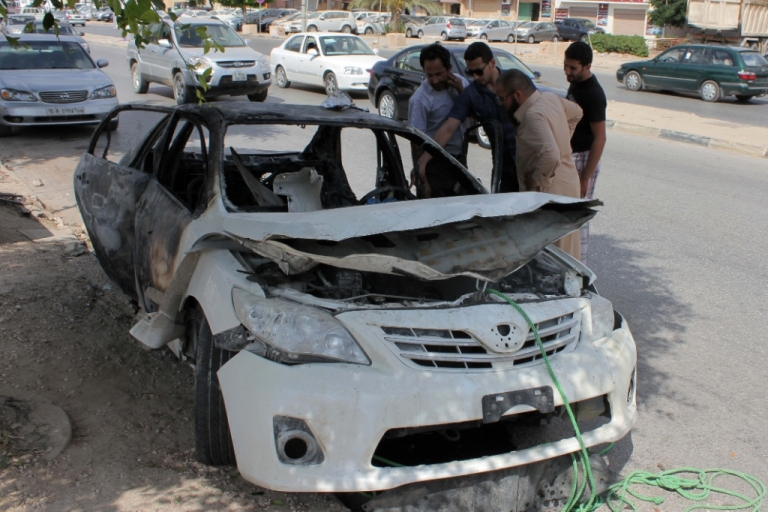 <p>Libyan men inspect the wreckage of a car on August 6, 2013 in the eastern Mediterranean city of Benghazi. A bomb exploded under a car in Benghazi killing the driver, a security official told AFP, the latest in a wave of violence to hit the restive city.</p>