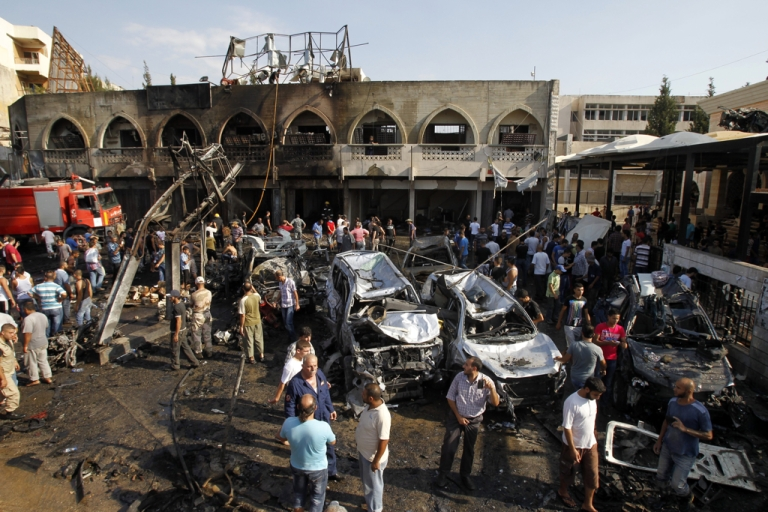 <p>Lebanese civilians gather next to the site of a blast outside the Al-Taqwa mosque in the northern city of Tripoli on August 23, 2013.</p>
