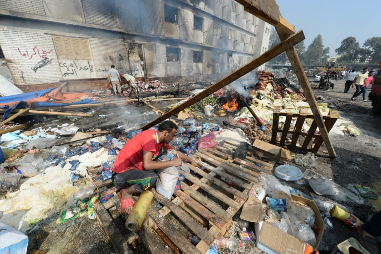 <p>An Egyptian garbage collector inspects the remains of the destroyed camp of ousted Mohammed Morsi supporters outside Rabaa al-Adawiya mosque on August 15, 2013 in Cairo, Egypt.</p>