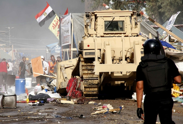 <p>Egyptian security forces move in to disperse a protest camp held by supporters of ousted president Mohamed Morsi and members of the Muslim Brotherhood, on Aug. 14, 2013 near Cairo's Rabaa al-Adawiya mosque.</p>