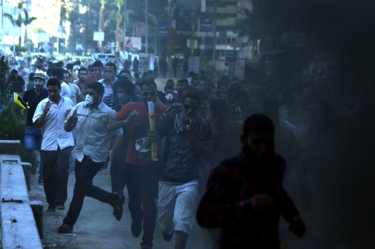 <p>Egyptian protestors run from tear gas during clashes in Cairo on Aug. 30, 2013.</p>