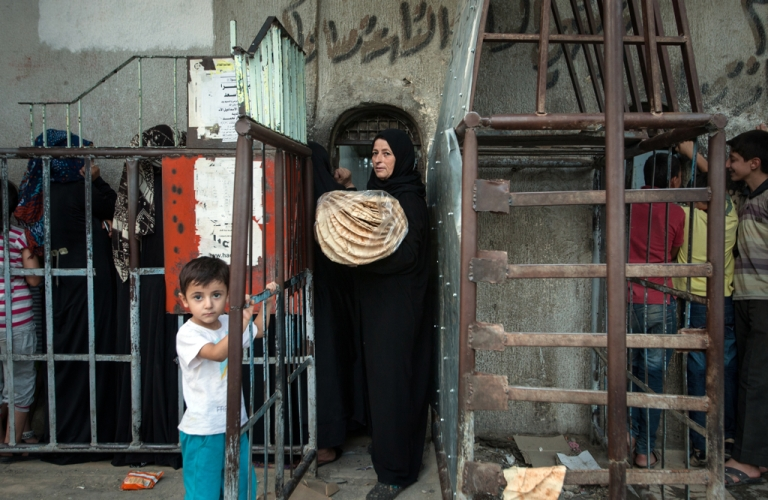 <p>A Syrian woman carrying a bag of bread exits a bakery run by the Islamic rebel group