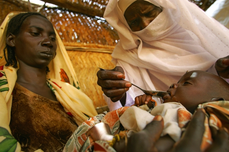 <p>A Sudanese mother holds her 12 day-old baby on her lap as a nurse feeds him medicine to fight diarrhea and dehydration 16 September 2004 at a Save the Children/US Aid Clinic in the Internally Displaced Persons camp of Krinding on the outskirts of the western town of El-Geneina.</p>
