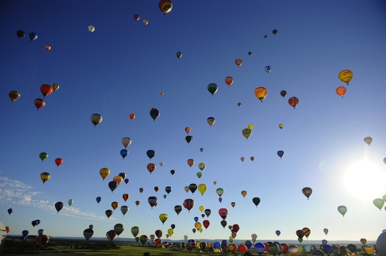 <p>Hot-air balloons fly over Chambley-Bussieres, eastern France, to try to set a world record with 408 balloons in the sky, on July 31, 2013, as part of the yearly event 'Lorraine Mondial Air Balloons,' an international air-balloon meeting.</p>