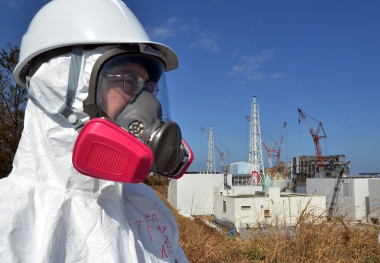 <p>A journalist looks at the stricken Tokyo Electric Power Co (TEPCO) Fukushima Dai-ichi nuclear power plant.</p>