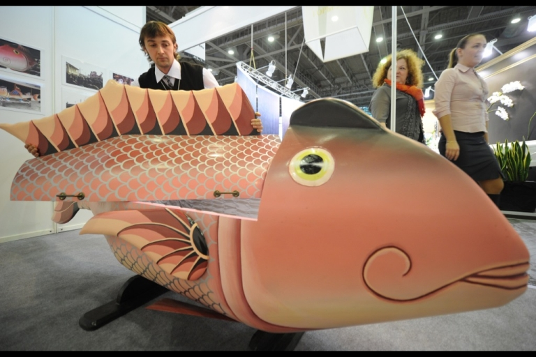 <p>A man stands next to a fish-shapped coffin made by Ghanaian born craftsman Eric Agetei Anang at the 10th annual Necropolis exhibition in Moscow, on October 27, 2011.</p>
