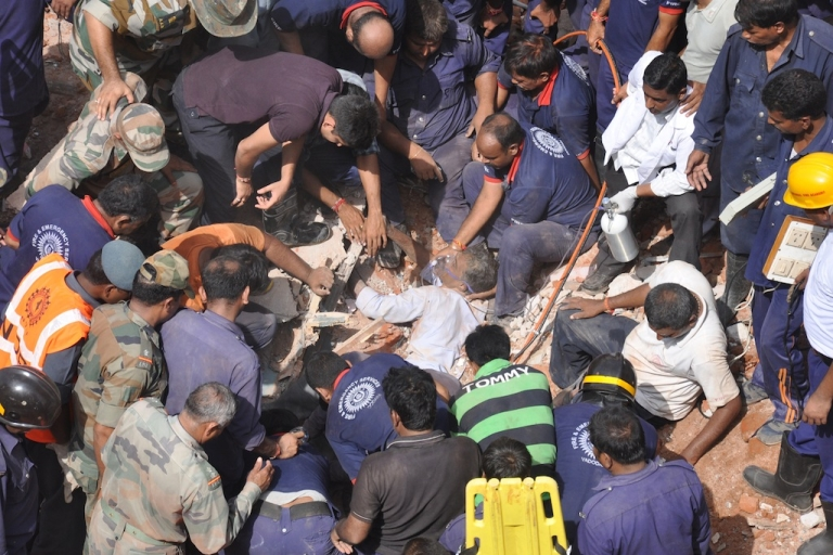 <p>Indian rescue personnel administer oxygen to an injured man (C) trapped in the debris of a collapsed residential building near Vadodara, some 110 kms from Ahmedabad, on August 28, 2013. Eleven residents were killed and another four injured and when the three-story residential building collapsed during pre-dawn hours.</p>