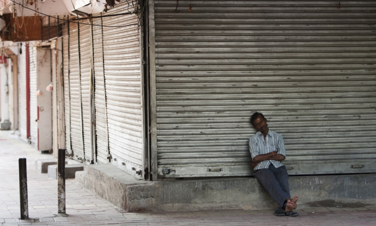 <p>A man sleeps in front of a closed business. Billions of dollars of foreign investment is leaving India, the government is scrambling to rein it in.</p>