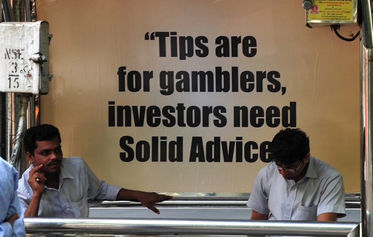 <p>Commuters sit next to a brokerage firm advertisement in Mumbai. India's rupee and stock exchanges have been plunging in recent days, as foreign investors pull money from an economy beset by bureaucracy and a current account deficit.</p>