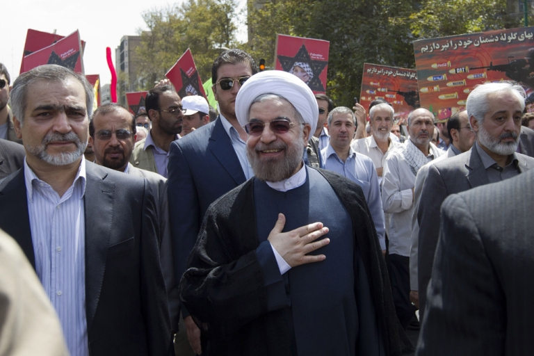 <p>Iranian president-elect Hassan Rowhani (C) takes part in a parade marking Al-Quds (Jerusalem) International Day in Tehran on August 2, 2013.</p>