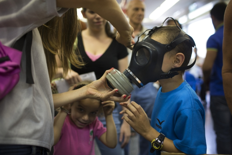 <p>An Israeli woman shows her children how to put on a gas mask as they pick their gas masks at a distribution center on August 26, 2013 in Tel Aviv, Israel. Israel keeps distributing gas masks to its civilian population as tension rises in Israel amid international talks of a military intervension In Syria.</p>