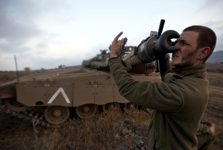 <p>An Israeli soldier checks a Merkava tank during a military exercise in the Israeli-annexed Golan Heights near the border with Syria on July 18, 2013.</p>