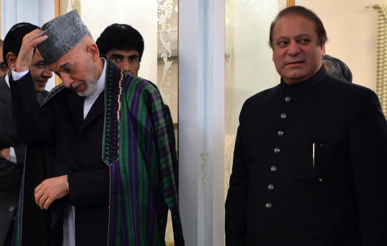 <p>Visiting Afghan President Hamid Karzai (L) adjusts his cap as he arrives with Pakistani Prime Minister Nawaz Sharif (R) for a press conference at The Prime Minister's House in Islamabad on Aug. 26, 2013.</p>