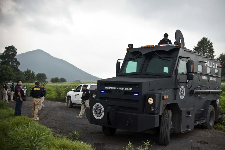 <p>Mexican police officers block a road leading to a park in the municipality of Tlalmanalco, some 20 miles southeast of Mexico City, where they discovered a mass grave.</p>