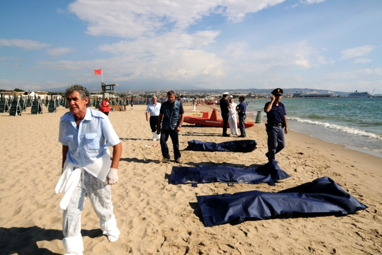 <p>Police and rescuers stand by the bodies of immigrants on a beach of the Sicilian city of Catania on Aug. 10, 2013. The bodies of six migrants from Africa were found on the beach while nearly 100 others, thought to be Syrians and some Egyptians, were rescued in the latest desperate attempt to reach Europe.</p>