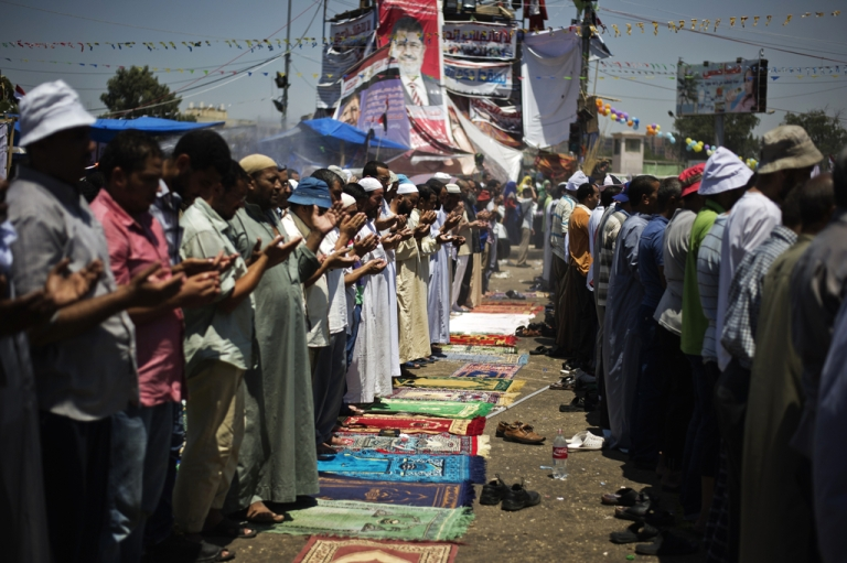 <p>Members of the Muslim brotherhood and supporters of ousted Egyptian President Mohammed Morsi perform noon prayers at a pro-Morsi sit-in outside the Rabaa al-Adawiya mosque on the first day of Eid al-Fitr celebrations on August 8, 2013 in Cairo.</p>
