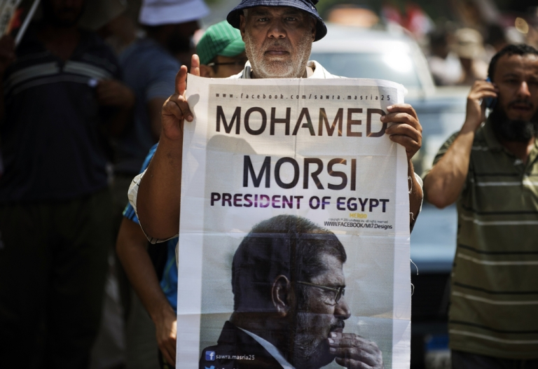 <p>A man holds a portrait of ousted president Mohamed Morsi. Morsi's Muslim Brotherhood may lose its status as an NGO as the military crackdown of the group continues.</p>