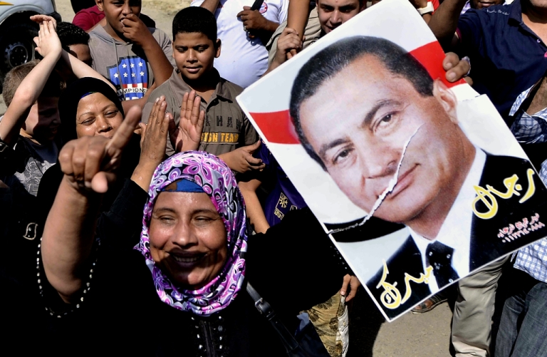 <p>An Egyptian supporter of former Egyptian president Hosni Mubarak raises up his portrait outside the Tora prison where Mubarak is detained, on August 22, 2013 in Cairo, Egypt. Egypt's toppled dictator Hosni Mubarak is expected to leave jail after a court ordered him released pending trial, but he will immediately be placed under house arrest.</p>