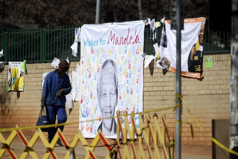 <p>A worker passes nearby a banner with well-wishing messages left for former South African President Nelson Mandela on July 19, 2013, outside the Medi Clinic Heart Hospital in Pretoria.</p>