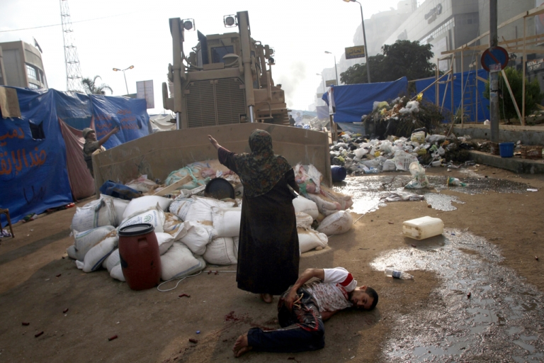 <p>An Egyptian woman tries to stop a military bulldozer from hurting a wounded youth during clashes that broke out as Egyptian security forces moved in to disperse supporters of Egypt's deposed president Mohamed Morsi in a huge protest camp near Rabaa al-Adawiya mosque in eastern Cairo on August 14, 2013.</p>