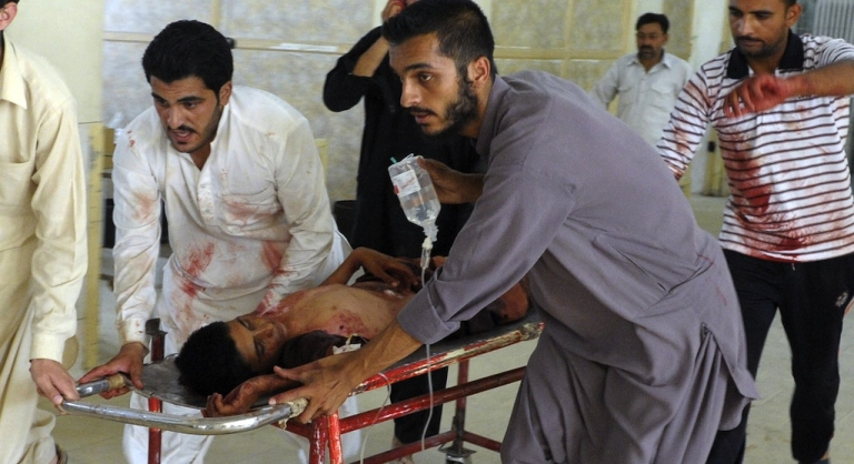 <p>Pakistani men carry an injured blast victim at a hospital in Quetta on August 8, 2013, following a suicide bomb attack at a policeman's funeral.</p>