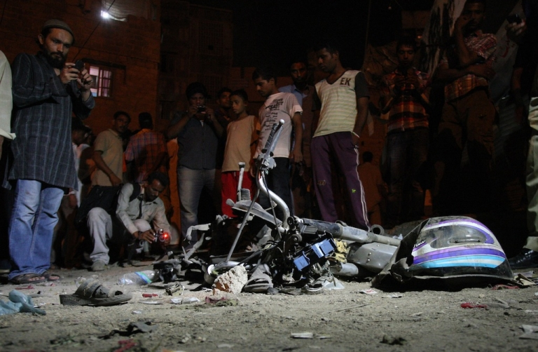 <p>Local residents gather at the site of the bomb explosion in the Pakistani port city of Karachi early on Aug. 7, 2013.</p>