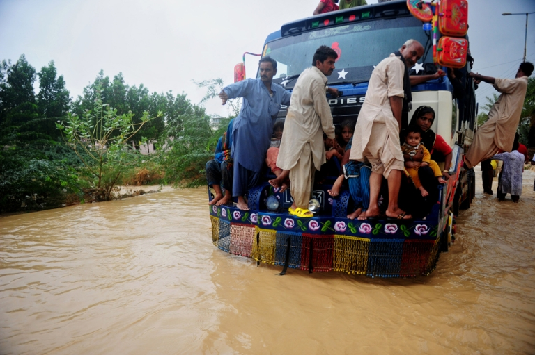 <p>Pakistani residents ride on a truck as they evacuate a flooded area in Karachi on August 4, 2013. At least 84 people have been killed across Pakistan after heavy monsoon rains caused flooding.</p>