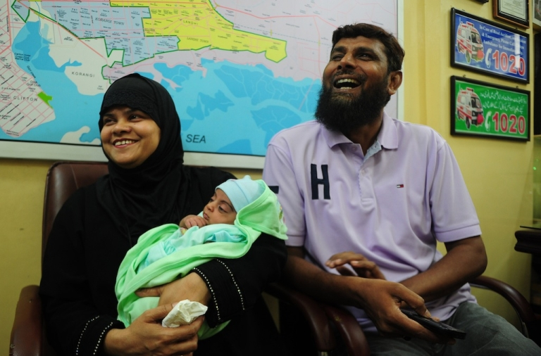 <p>Pakistani couple Riazuddin (R) and his and wife Tanzeem laugh as they hold their adopted daughter Fatima at The Chhipa Welfare Association in Karachi on Aug. 1, 2013.</p>