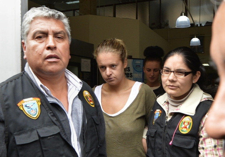 <p>Melissa Reid (C), a British woman arrested on August 6, 2013 at Lima's airport carrying cocaine in her luggage is escorted out of the Callao prosecutors building on August 20, 2013, to be taken to the district court with her companion Michaella McCollum, 20, (background)..</p>