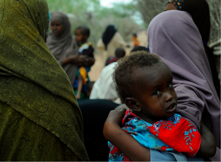 <p>A young Somali refugee waits with her mother to be vaccinated at a pediatric vaccination centre at Hagadere refugee site within the Dadaab refugee complex in Kenya's north-east province on August 1, 2011.</p>