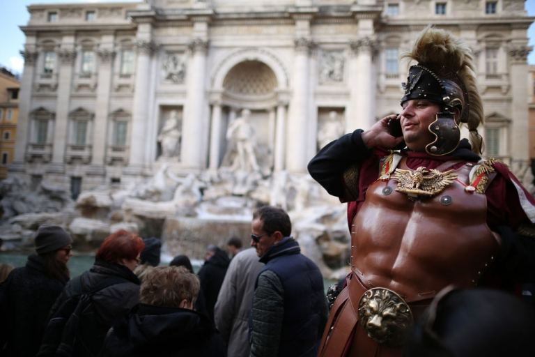<p>A tourist guide talks on a cellphone at the Trevi Fountain on March 16, 2013 in Rome, Italy.</p>