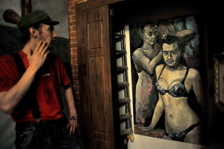 <p>A visitor looks at an artwork representing President Vladimir Putin and Prime Minister Dmitry Medvedev by Russian artist Konstantin Altunin during the